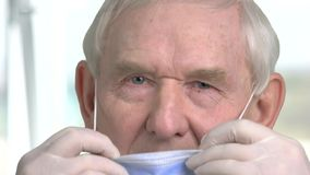 Close up portrait old doctor put on protective mask. Senior dentist put on mask, blurred bright background stock video footage