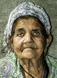 Close up portrait of old homeless Gypsy beggar woman with wrinkled face skin begging for money on the street in the city and looki. Ng in the camera with sad stock photo