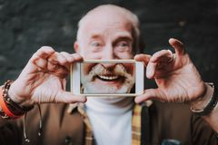 Stylish old man is holding smartphone in hands stock photos
