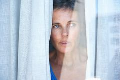 Close up older woman looking opening curtains and looking through window. Close up portrait of older woman looking opening curtains and looking through window Royalty Free Stock Photo