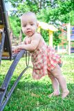 Close up. Portrait of a one-year-old 9 months child in a pink sundress. The girl is learning to walk, standing barefoot. Close up. Portrait of a one-year-old 9 royalty free stock image