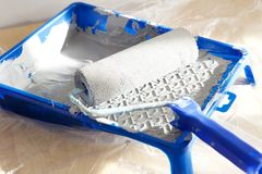 Wall painting tools. Close up portrait of paint roller in paint tray with color in the tray Royalty Free Stock Photo