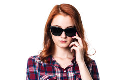 Close-up portrait of a pensive girl with dark glasses. The girl with red hair in a checkered shirt Royalty Free Stock Photo