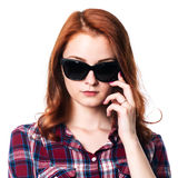 Close-up portrait of a pensive girl with dark glasses. Girl with red hair in a checkered shirt Stock Photography