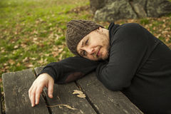 Close up portrait pensive man with wool hat laying on a bench. A Royalty Free Stock Images