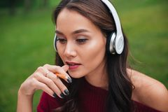 Close up portrait of a pensive young asian girl. In headphones holding pencil at her mouth while sitting outdoors Stock Photo