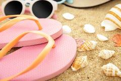 Pink flipflops, sunglasses, and seashells on beach sands. Close up portrait of pink flipflops, sunglasses, and seashells on beach sands Stock Photos