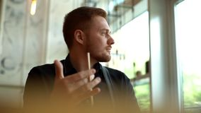 Close-up portrait of ponder young man in office. Designer plans his work. And holding a pencil in his hand. Shooting is slow motion from below stock footage