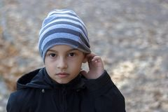 Close-up portrait of a poor child with hearing problems, holding his hand near his ear, showing me that he does not hear. Child in autumn clothes in the Park stock photos