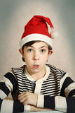 close up portrait of a preteen boy in santa hat Royalty Free Stock Images
