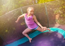 Cute girl having fun jumping on the trampoline royalty free stock images