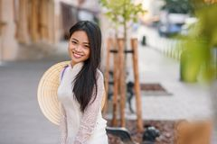 Close up portrait of pretty asian girl dressed in Ao Dai dress with vietnamese conical hat against arches background. Close up portrait of pretty asian girl stock image