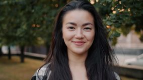 Close-up portrait of pretty Asian student smiling standing alone in urban park