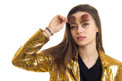 Close up portrait of pretty brunette woman in round sunglasses and golden jacket looking at the camera. Isolated on white background Stock Images