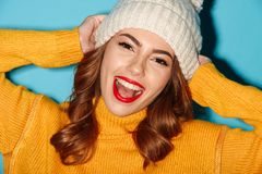 Close up portrait of pretty cheerful girl in winter hat. Looking at camera  over blue background Stock Photo
