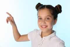 Close-up portrait of a pretty child girl smiles and points with her finger Royalty Free Stock Image