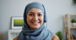 Close-up portrait of pretty Muslim woman in hijab smiling looking at camera. Indoors in apartment. Individuality, modern people and lifestyle concept stock video