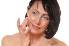 Close up portrait of pretty senior woman using face cream. Beauty and care concept Royalty Free Stock Images