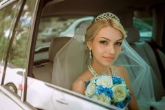 Close-up portrait of a pretty shy bride in a car window Stock Image