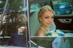 Close-up portrait of a pretty shy bride in a car window Royalty Free Stock Photography