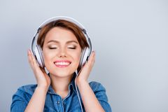 Close up portrait of pretty smiling girl in headphones enjoying. Her favourite song Royalty Free Stock Photography