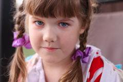 Close up portrait of pretty smiling little girl with braids with Stock Photo