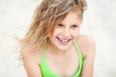 Close-up Portrait of a pretty smiling little girl with waving in Stock Photography