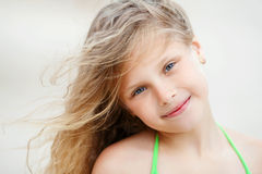 Close-up Portrait of a pretty smiling little girl with waving in Royalty Free Stock Image