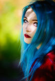 Close-up portrait of pretty young girl with blue hair. Close-up portrait of a pretty young girl with blue hair Stock Photo