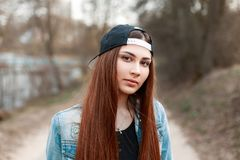 Close-up portrait of a pretty young woman in a black baseball ca. P and a denim jacket Royalty Free Stock Images