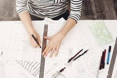 Close up portrait of professional young beautiful female architect in striped clothes, doing her drawings with ruler and. Pen, working with interest on new stock photos