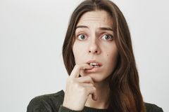 Close-up portrait of puzzled confused woman with dark long hair dressed casually, looking at camera with puzzlement. Close-up portrait of puzzled and confused Stock Images