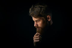 Close-up portrait of puzzled young man touching beard looking do Stock Images