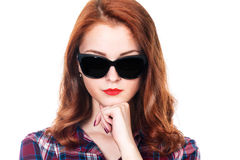Close-up portrait of red-haired girl with dark glasses. Friendly cute girl in a checkered shirt. Isolated on a white background Royalty Free Stock Photos
