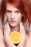 Close up portrait of redhaired woman with orange half. Close up portrait of young redhaired woman with orange half Stock Image
