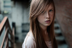 Close-up portrait of a redhead girl with freckles and blue eyes standing on the stairs and looking at camera. Horizontal photo Royalty Free Stock Images
