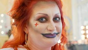 Close-up portrait of redhead woman with halloween makeup at beauty salon. Close-up funny portrait of redhead woman with halloween makeup at beauty salon. Face of Stock Photo