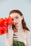 Close up portrait of a redheaded woman holding tulip flowers. Fashion portrait of a beautiful redheaded woman holding tulip flowers and looking at camera Royalty Free Stock Photo