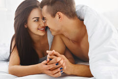 Close up portrait of romantic couple in bed. Close up portrait of romantic young couple in bed at home. Relationships, love, closeness stock photo