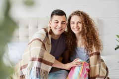 Close up portrait of romantic couple in love sitting under warm plaid in bedroom, embrace each other and have positive facial royalty free stock photos