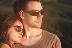 Close-up Portrait of a romantic young hipster couple hugging. They stand in an embrace in nature high in the mountains. Against the backdrop of a mountain green stock image