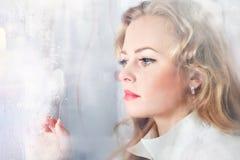 Close-up portrait of a sad beautiful woman near the window Royalty Free Stock Image