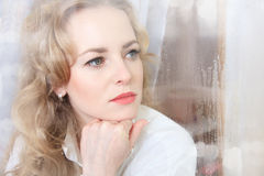 Close-up portrait of a sad beautiful woman near the window Stock Images