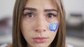 Close-up portrait of a sad crying young woman looking at the camera. Blue message box with zero painted on the girl`s