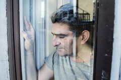 Close up portrait of sad and depressed 40s man looking through w. Indow glass reflection lonesome and thoughtful suffering depression thinking and feeling low in Stock Photography