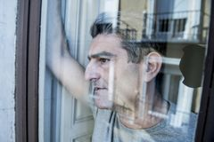 Close up portrait of sad and depressed 40s man looking through w. Indow glass reflection lonesome and thoughtful suffering depression thinking and feeling low in Royalty Free Stock Photos