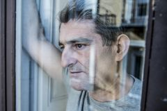 Close up portrait of sad and depressed 40s man looking through w. Indow glass reflection lonesome and thoughtful suffering depression thinking and feeling low in Stock Image