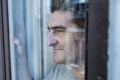Close up portrait of sad and depressed 40s man looking through w. Indow glass reflection lonesome and thoughtful suffering depression thinking and feeling low in Royalty Free Stock Images
