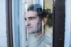 Close up portrait of sad and depressed 40s man looking through w. Indow glass reflection lonesome and thoughtful suffering depression thinking and feeling low in Royalty Free Stock Photography