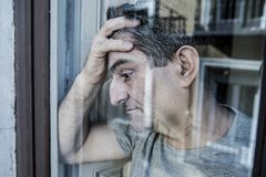 Close up portrait of sad and depressed 40s man looking through w. Indow glass reflection lonesome and thoughtful suffering depression thinking and feeling low in Royalty Free Stock Image